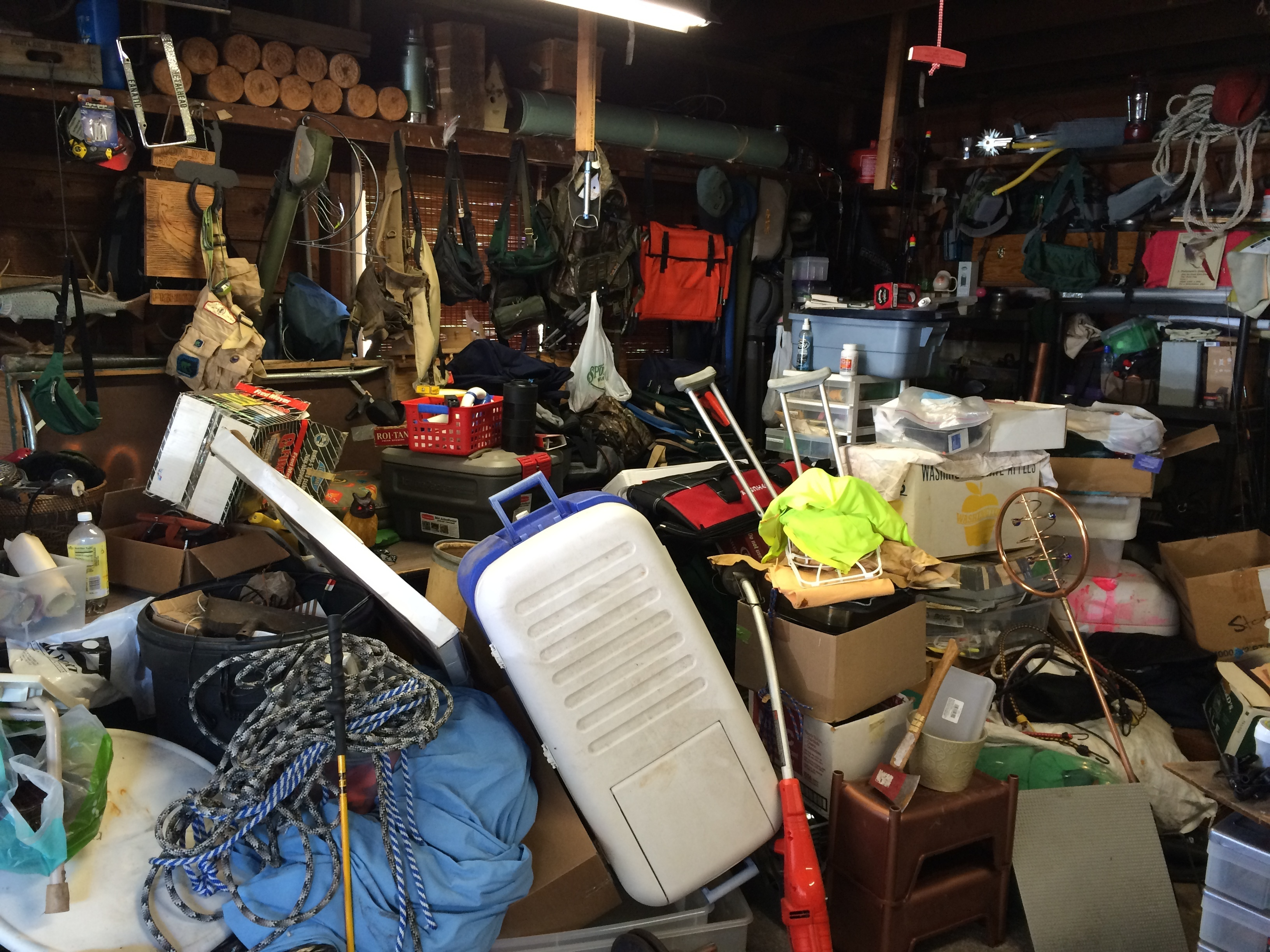A garage filled with random items; bikes, toys, boxes, tools, etc