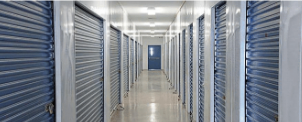 Hallway of an indoor storage unit facility with blue doors
