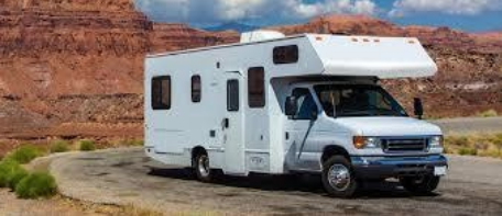 White RV in front of red rocks