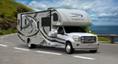 White and black class C motorhome RV on a scenic ocean cliffside road