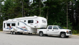 Large white fifth wheel RV being pulled by a white heavy-duty truck