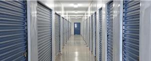 A hallway of blue indoor storage units