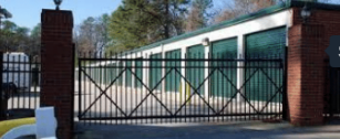 Green and tan storage units behind a secure black fence