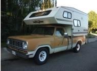 Truck camper RV on a vintage orange truck