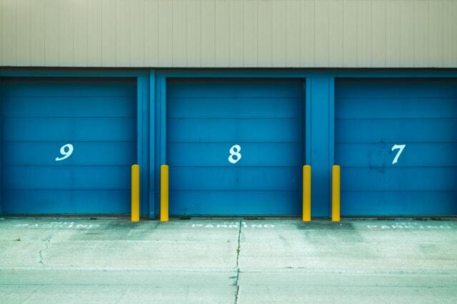 Three storage units with blue doors in a row