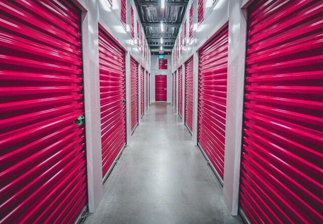 Indoor hallway of storage units with red doors