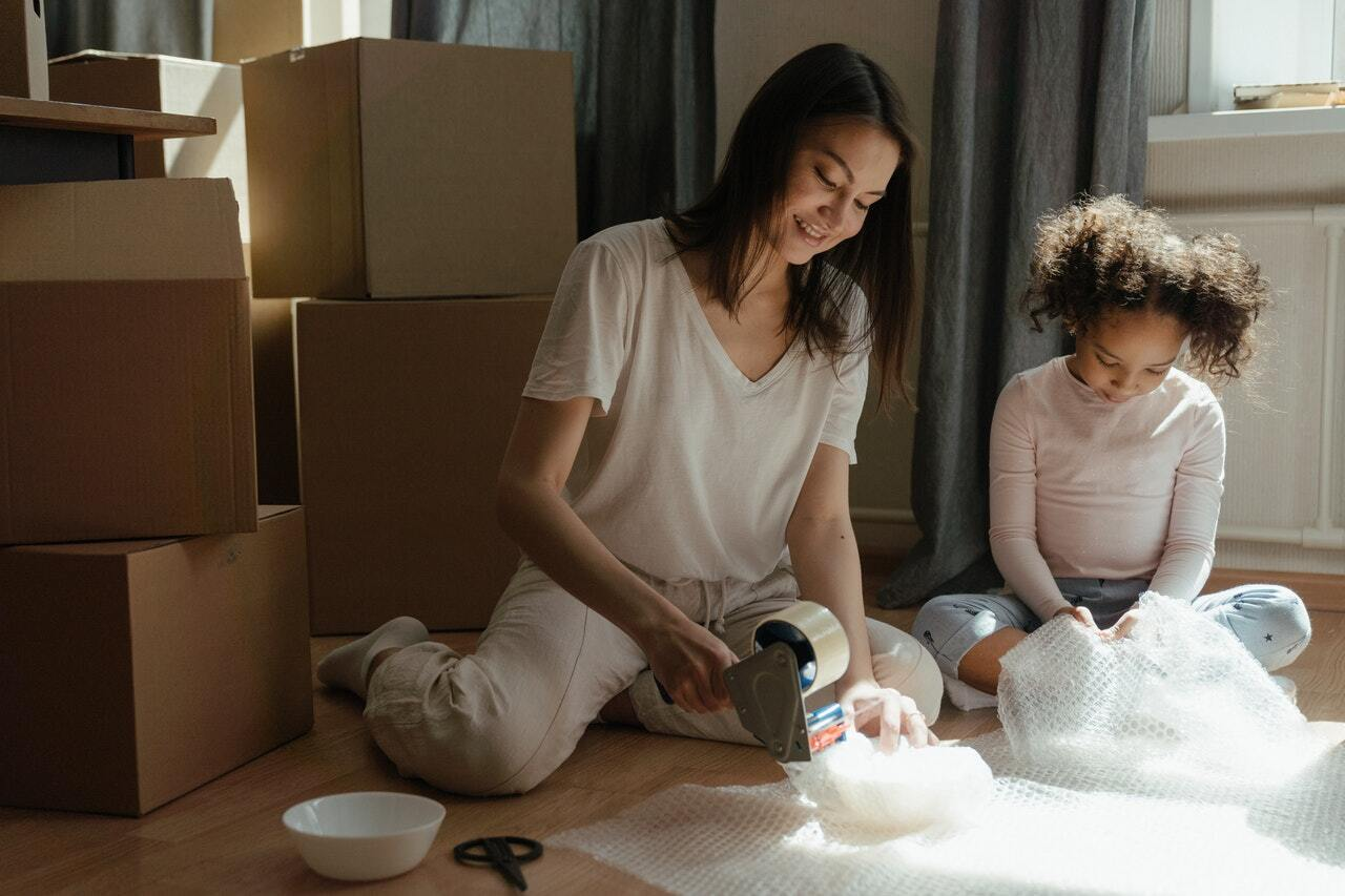 A mother and daughter packing their possessions in cardboard boxes