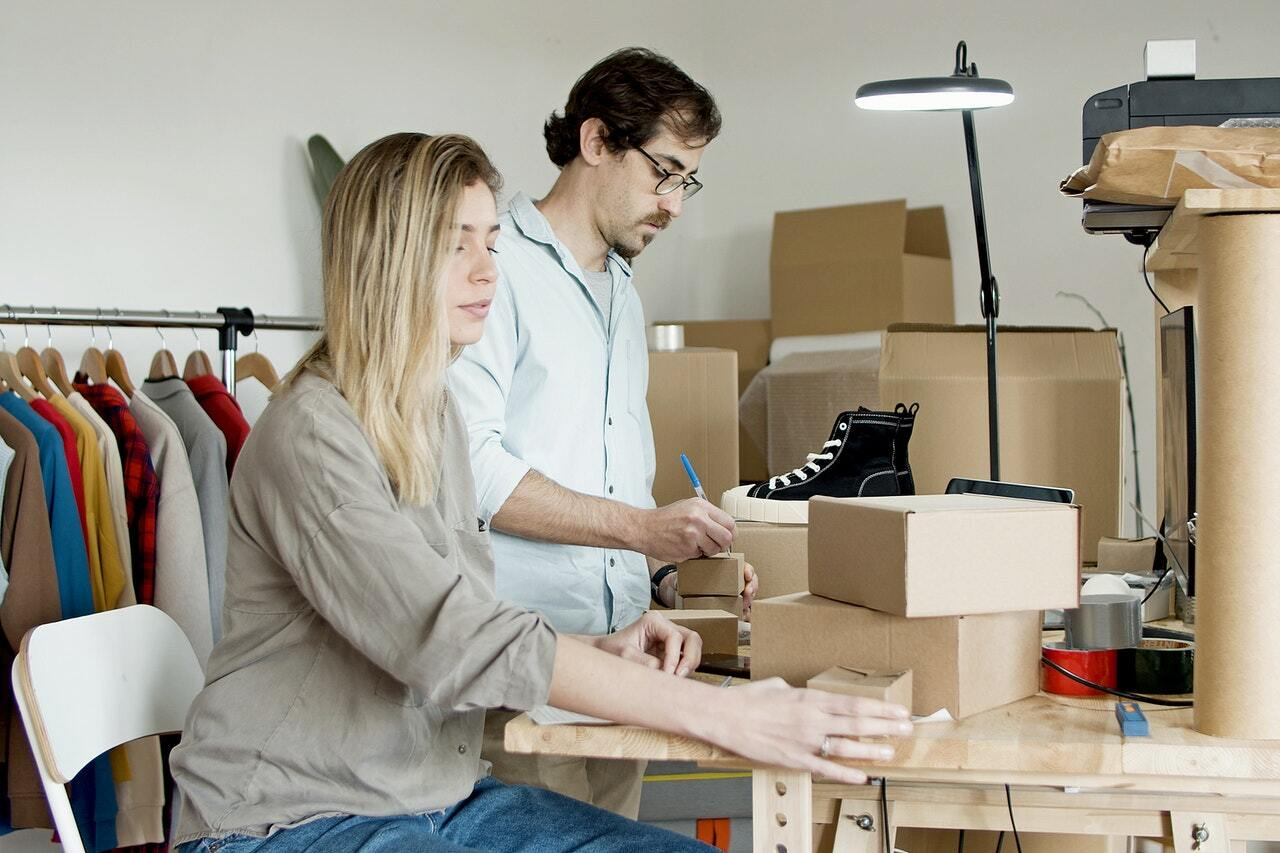 A man and a woman in a room with cardboard boxes labeling them